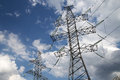Electricity pylons and line against the blue sky clouds Stock Photo