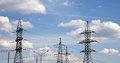Electricity pylons and line against the blue sky clouds Royalty Free Stock Image