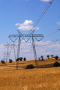 Electricity pylons and overhead cables receding through countryside fields under blue cloudy sky Stock Photo