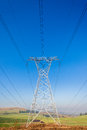 Electricity tower power lines cables landscape electrical steel line crossing over the green and blue sugarcane farming to supply Royalty Free Stock Image