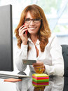 Electronic banking online shopping portrait of beautiful mature smiling woman using a computer and her mobile phone while holding Royalty Free Stock Images
