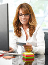 Electronic banking online shopping portrait of beautiful mature smiling woman using a computer while holding a credit card in Stock Images