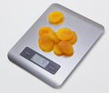 Electronic kitchen scale with dried apricots isolated scales on the grey back Royalty Free Stock Photos