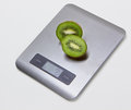 Electronic kitchen scales with kiwi isolated sliced on the grey back Stock Image