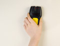 Electronic stud finder against interior wall of home photo female hand holding white Stock Images