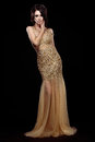 Elegance. Aristocratic Lady in Golden Long Dress over Black Background Royalty Free Stock Photo