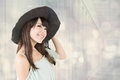 Elegant asian woman with hat young black posing against bokeh background Stock Image