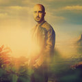 Elegant bald male in leather jacket on sunset in the mountains Royalty Free Stock Photo