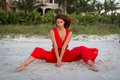 Elegant beautiful barefoot young woman sitting beach sand wearing stylish red outfit Stock Photo