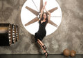 Elegant and beautiful top model near ventilation pipes posing with huge turbo ventilator behind her were lights coming