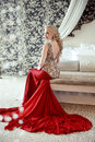 Elegant blond woman model wearing in luxurious red gown with lon Royalty Free Stock Photo