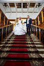 Elegant bride and groom in stairs with red carpet Royalty Free Stock Photo