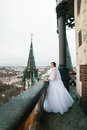 Elegant bride poses on the tower balcony of old gothic cathedral Royalty Free Stock Photo