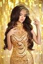 Elegant brunette in golden evening dress. Fashion Glamour style. Royalty Free Stock Photo