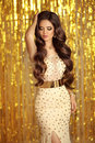 Elegant brunette in golden sparkling dress. Fashion Glamour style. Beautiful stunning woman with long wavy hair style posing over Royalty Free Stock Photo