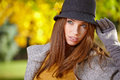 Elegant brunette woman in a park in autumn standing Royalty Free Stock Image