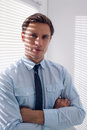 Elegant businessman with arms crossed in office portrait of an young standing Royalty Free Stock Images