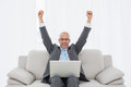 Elegant businessman cheering in front of laptop at home with clenched fists on sofa living room Royalty Free Stock Photography