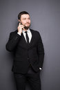 Elegant businessman having a serious conversation on a smart phone against a dark background Royalty Free Stock Photo
