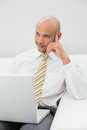 Elegant businessman with laptop sitting on sofa at home smiling young Royalty Free Stock Photo