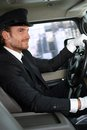 Elegant chauffeur driving luxurious car smiling Stock Photography