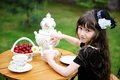 Elegant child girl having a tea party outdoors Stock Image