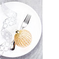 Elegant christmas table setting with festive decorations on whit white plate isolated shiny golden ball fork and knife Royalty Free Stock Images