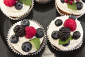 Elegant Cupcakes with Berries on the Black Plate Royalty Free Stock Photo