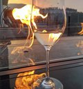Glass of white wine by fireside with sunset in the background Royalty Free Stock Photo