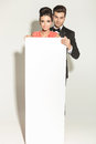 Elegant fashion couple holding a white empty board Royalty Free Stock Photo