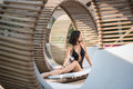 Elegant female with a perfect body sitting in profile on a wooden lounger on the luxury resort Royalty Free Stock Photo