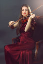 Elegant fiddle player beautiful girl in red dress plays a and looks at camera Stock Photo