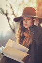 Elegant girl with a book in warm autumn light beautiful and poses Stock Photography