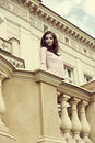 Elegant girl on retro balcony pretty with pink dress posing of old building in outdoor fashion portrait Stock Photo