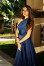 Elegant girl young woman wearing blue evening dress posing against palms at sunset and looking in camera Stock Photos