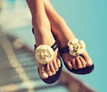 Elegant girls legs pedicure with the nails graceful female feet in beautiful flip flops on beach Royalty Free Stock Images