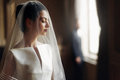 Elegant gorgeous bride gently looking under veil at stylish groo Royalty Free Stock Photo