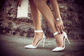 Elegant high heel shoes woman legs in white outdoor shot in the city summer day Royalty Free Stock Image