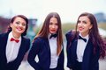 Elegant ladies in black suits outdoors three Royalty Free Stock Photos