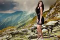 Elegant lady in dress standing on the mountain rocks high fashion young mini Stock Photography