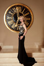 Elegant lady in fashion long black dress posing in front of wall clock Royalty Free Stock Photo