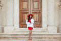 Elegant lady. Fashion woman in red hat and dress wearing in whit Royalty Free Stock Photo