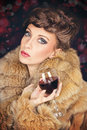 Elegant lady in fur coat celebrating christmas drinking wine gorgeous young with fashionable hair style wearing brown dark blurred Royalty Free Stock Photography