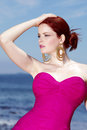 Elegant lifestyle female red head posing for fashion shoot by the ocean Royalty Free Stock Images