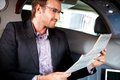 Elegant man reading papers in luxury car young newspaper Royalty Free Stock Photography