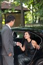 Elegant men helping his lady coming out of a car Stock Photo