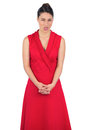 Elegant model in red dress sticking her tongue out on white background Royalty Free Stock Image