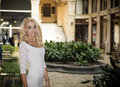Elegant pretty blonde young woman in posh city setting in europe standing white dress Royalty Free Stock Images