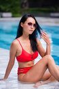 Elegant woman in the red bikini on the sun-tanned slim and shapely body is posing near the swimming pool Royalty Free Stock Photo