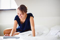 Elegant, smart, young woman using her tablet computer in bed Royalty Free Stock Photo